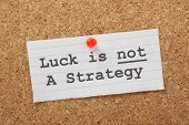 The phrase Luck is not a Strategy on a cork notice board as a reminder that your business or life plans cannot succeed on good fortune alone poster
