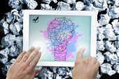 Composite image of hand touching tablet showing light bulb on paint splashes poster