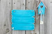 Antique blank teal blue sign with teal blue and pink birdhouse with wooden hearts hanging on rustic fence poster