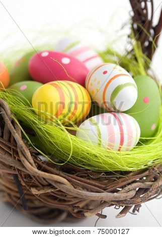 Colorful painted easter eggs in brown basket