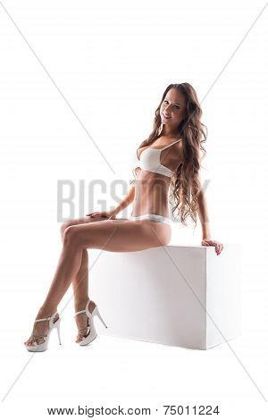 Beddable lingerie model posing sitting on cube