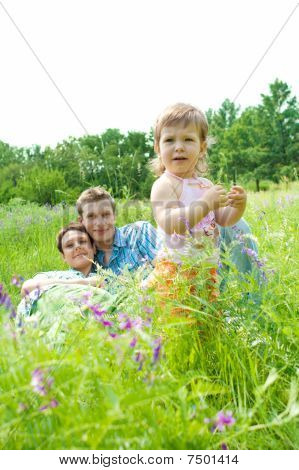 Toddler And Her Parents In The Meadow