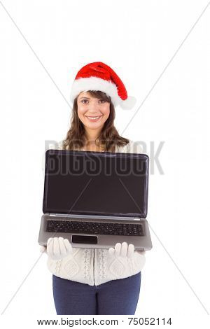 Smiling brunette in santa hat showing her laptop on white background
