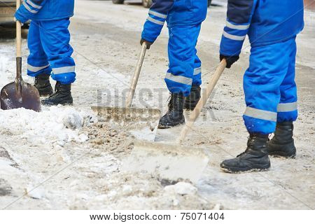 municipal urban servicing workers shoveling snow during winter road cleaning