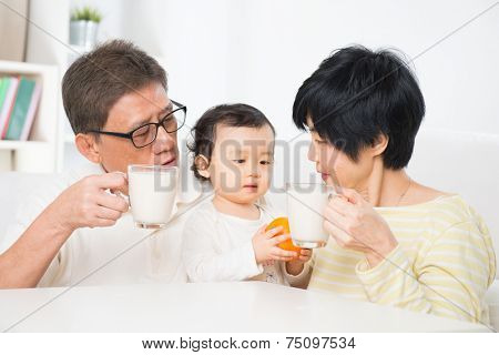 Asian family drinking milk, grandparents and grandchild indoor living lifestyle at home.