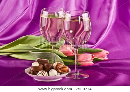 Two Glasses Of White Wine, Flowers And Sweets