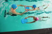 Cute swimming class in pool with coach at the leisure center poster