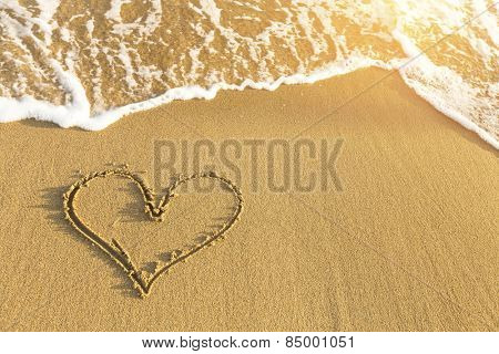 Heart drawn in sea beach sand, soft wave in a Sunny summer day.
