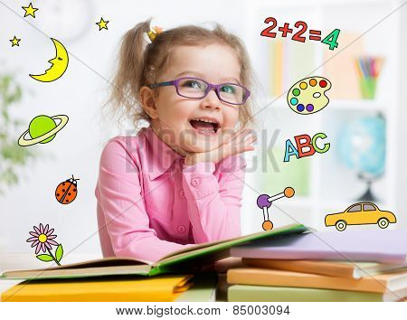 Funny smart kid in eyeglasses reading book in kindergarten