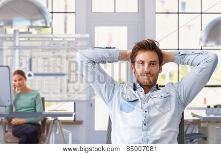 Young man taking break of work at trendy architect office