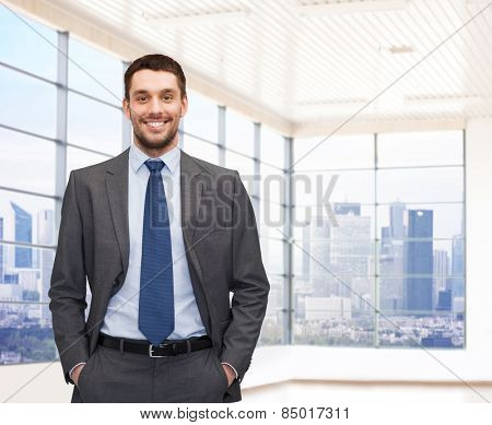 business, people and office concept - happy young businessman over office room or new apartment background