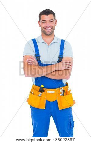 Portrait of happy repairman in overalls wearing tool belt standing arms crossed on white background