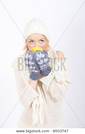 beautiful winter frozen woman with drinking hot tea from yellow cup