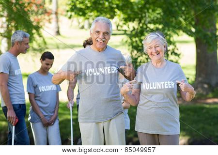 Happy volunteer senior couple smiling at the camera on a sunny day