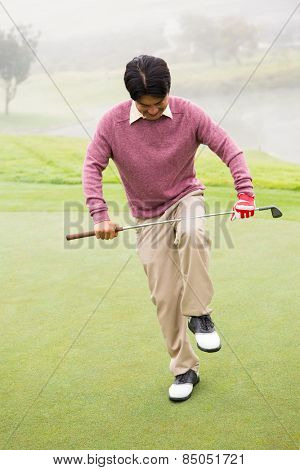 Angry golfer trying to brake his club at the golf course