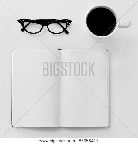 high-angle shot of a blank notebook, a pair of black plastic-rimmed eyeglasses for women and a cup of coffee on a white table