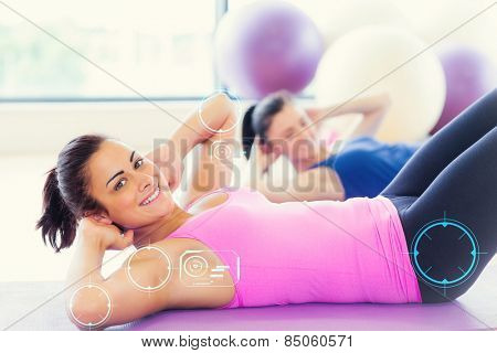 Two fit young women doing pilate exercises against fitness interface