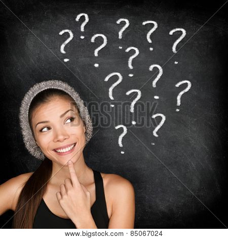 Student thinking with question marks on blackboard. Asian female young adult university or college student looking up at written drawings of question marks on chalkboard wondering career choices. poster