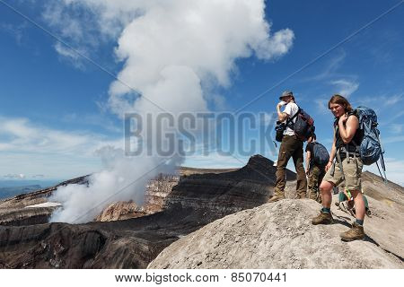 Tourists In Crater Of Active Gorely Volcano Watching At Volcano Fumaroles. Russia, Kamchatka