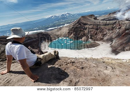 Tourist In Crater Of Active Gorely Volcano Watching At Beautiful Crater Lake. Russia, Kamchatka