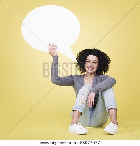 Friendly woman being joyful holding a white blank speech bubble with empty copy space, isolated on yellow background.