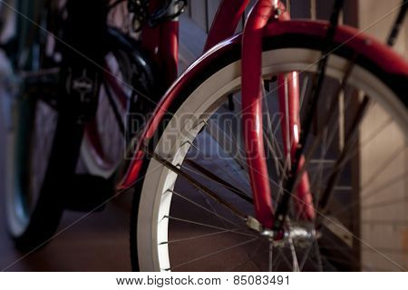 Close up of the front of a red bicycle with whitewall tires leaning against a carport wall, tilt-shift soft focus filter.