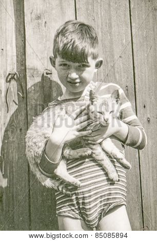 Vintage photo of little boy with a cat, 1950's