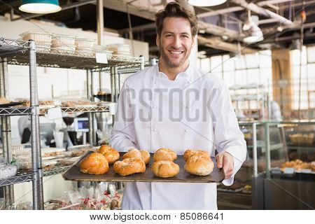 Cheerful baker holding tray of bread at the bakery