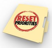Reset Priorities words stamped on a manila folder to illustrate a change in the most important jobs or tasks to handle first in order poster