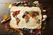 Map of world made from different kinds of spices on wooden background poster