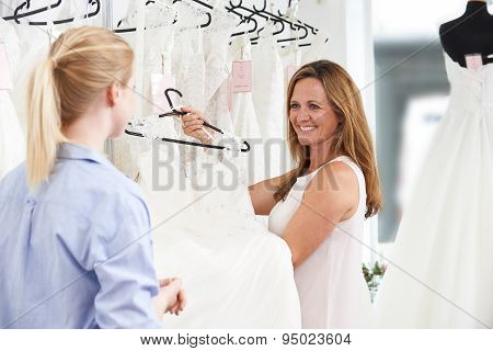 Sales Assistant In Bridal Store Helping Bride To Choose Wedding Dress poster