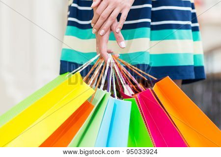 A lady in a skirt is holding a lot of colourful shopping bags. poster