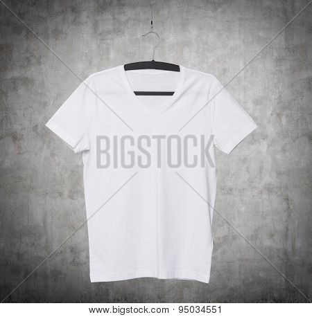 Close Up Of A V Shape White T-shirt On Cloth Hanger. Concrete Background.