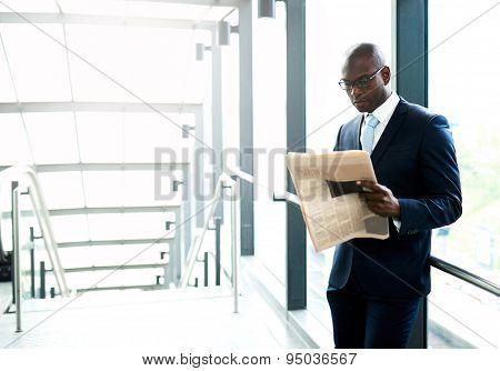 Businessman Reading A Newspaper Inside A Building