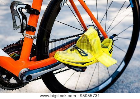 Close-up of black rear wheel of the bicycle, an orange frame, bright yellow cycling shoe in the foreground ready to start cycling stage competitions in a triathlon. poster