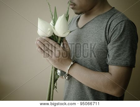 Young Man In Handcuffs And Lotus In Hand