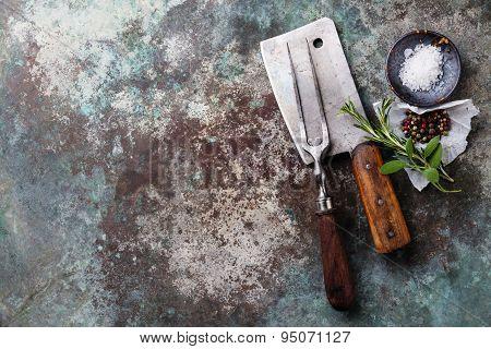 Vintage Meat Fork And Cleaver With Seasonings On Metal Background