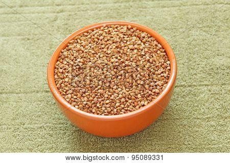 Buckwheat In Brown Ceramic Bowl On Taupe Fabric Taken Closeup.