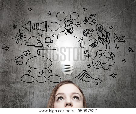 Young Business Lady Is Looking For New Business Ideas. Drawn Business Icons On The Concrete Wall And
