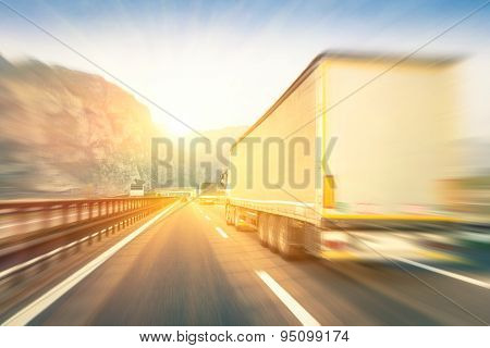 Generic Semi Trucks Speeding On The Highway At Sunset - Transport Industry Concept With Semitruck