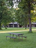 A picnic table in the green wooded lawn of park ready picnickers. A pavilion is in the background. poster