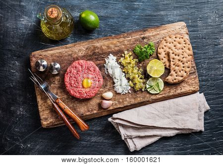 Beef tartare on cutting board with pickled cucumber and fresh onions on dark background, top view with copy space