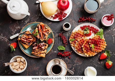Breakfast table with waffles, yogurt, coffee and fresh fruits and berries on black background, top view