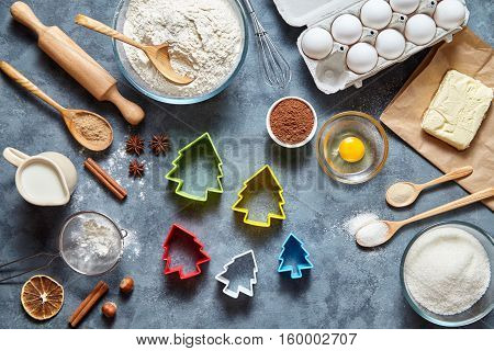 The process of making gingerbread cookies. Baking ingredients for homemade pastry on dark background. Bake sweet cake dessert concept. Top view, flat lay style.