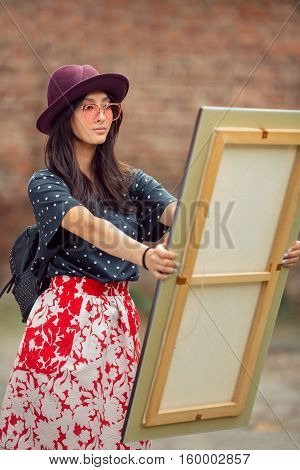 Young Asian woman with painting outdoors. Mixed race student girl on university college campus park looking at picture in wooden frame.
