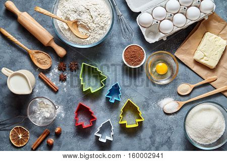 The process of making gingerbread Christmas tree cookies. Baking ingredients for homemade pastry on dark background. Bake sweet cake dessert concept. Top view, flat lay style