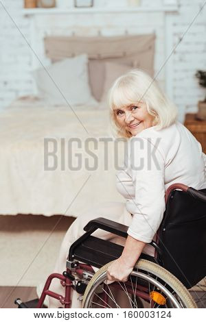 Catch the moment. Pleasant delighted aged disabled woman sitting in the wheelchair and smiing while resting at home