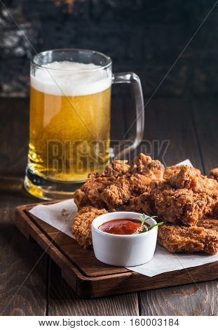 Buffalo style chicken wings served with cold beer on wooden background