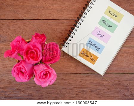Handwriting Vision Mission Goal Strategy Action Plan on notebook and sweet pink rose with dark wood background (Top view)