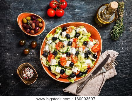 Greek salad with fresh vegetables, feta cheese and black olives on black background, top view with copy space